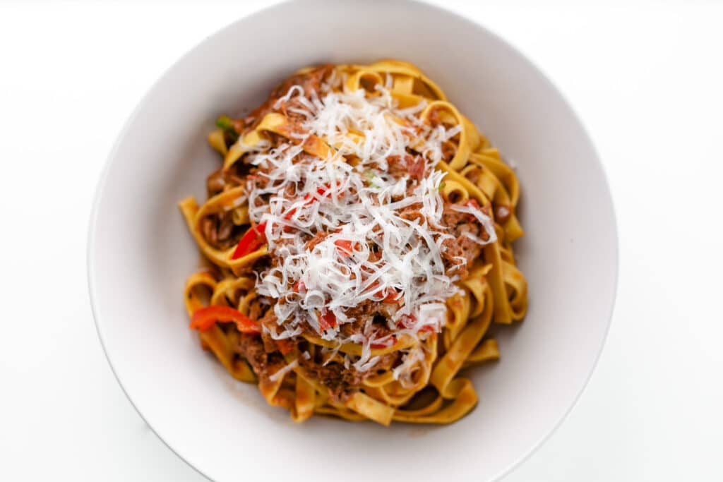 beef ragu pasta topped with parmesan
