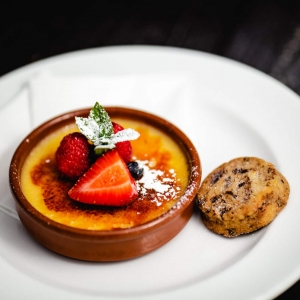 Lemon Creme Brule topped with summer berries, served with a dark chocolate shortbread