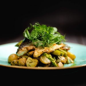 Seared sea-bass fillet with sautéed spring onions and parsley potatoes, buttered asparagus, chilli, garlic and coriander butter
