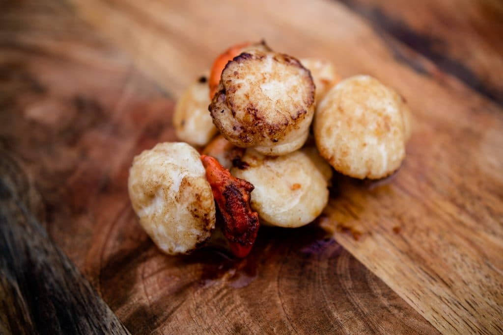 Freshly cooked scallops on a wooden board