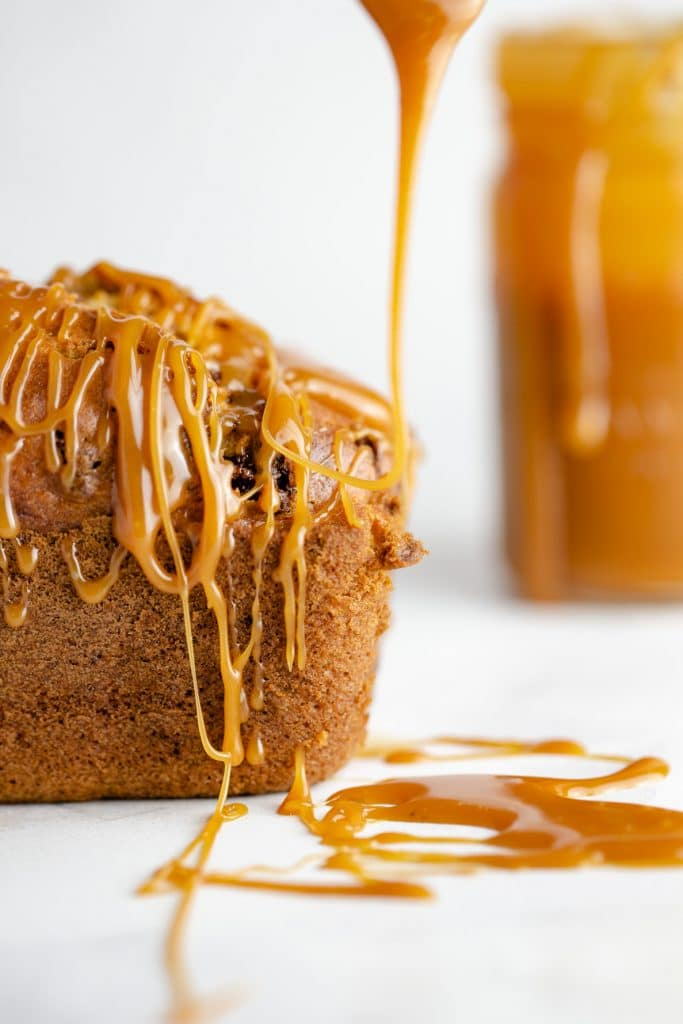 Salted caramel sauce being drizzled onto a chocolate banana bread