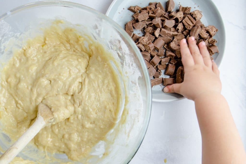 Child's hand reaching out to a plate of chocolate