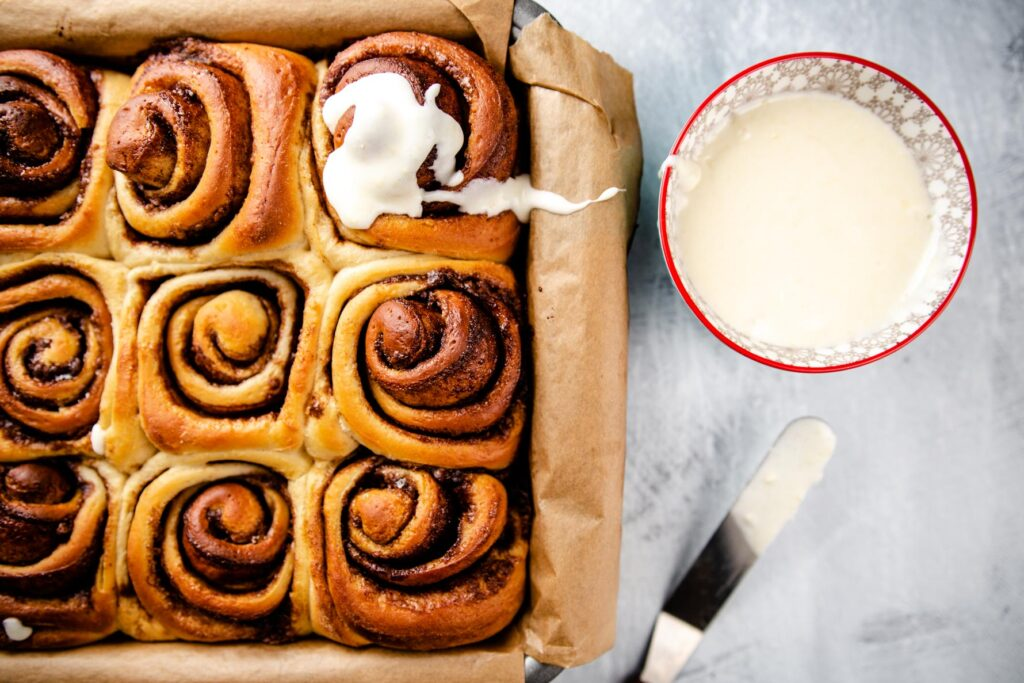 Top down image of cinnamon rolls with frosting on some